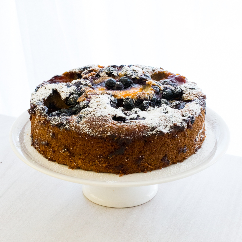 Peach Tea Cake decorated with peaches and blueberries.